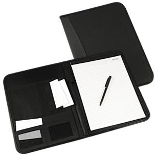 Carpeta de PU/PVC. En el interior incluye Block de 30 hojas lineadas tamaño A4, Bolígrafo negro a pasta, Bolsillos para documentos tamaño A4, Bolsillos de tela TNT y Compartimentos para Tarjetas.